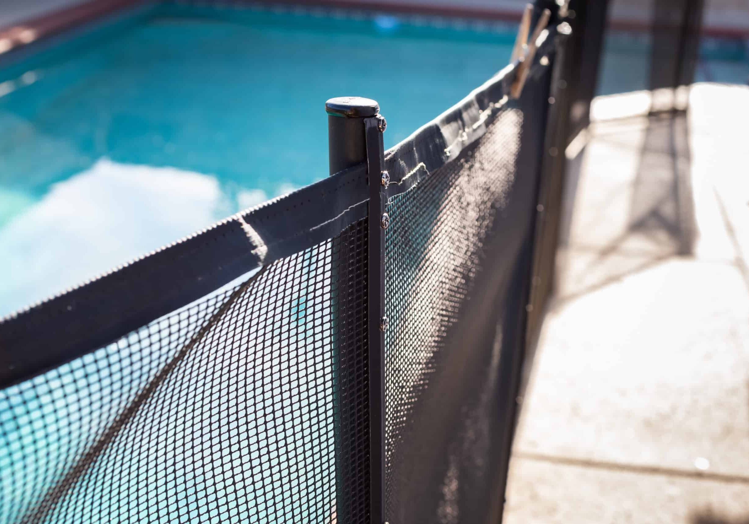 A closeup view of a swimming pool fence post, in a home backyard setting.